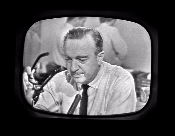 American broadcast journalist Walter Cronkite removes his glasses while announcing the death of President John F. Kennedy as seen from a television monitor, November 22, 1963. (Photo by CBS Photo Archive/Getty Images)